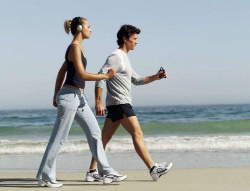 жена и мъж, които тренират на плажа
