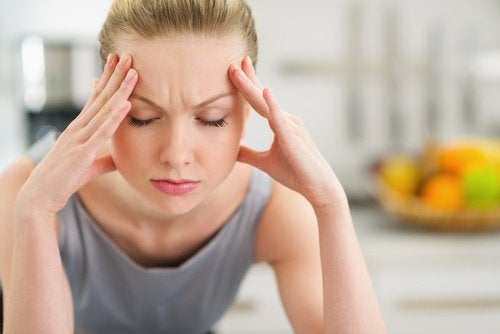 жена, която се държи с две ръце за главата и изглежда стресирана