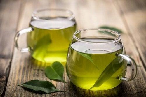 Диуретични чайове: Зелен чай в две стъклени чаши и листа от зелен чай, на маса