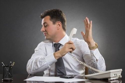Мъж с вдигната настрани слушалка на телефон