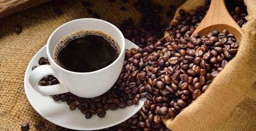 На празен стомах: чаша с кафе и разпилени зърна от кафе около нея