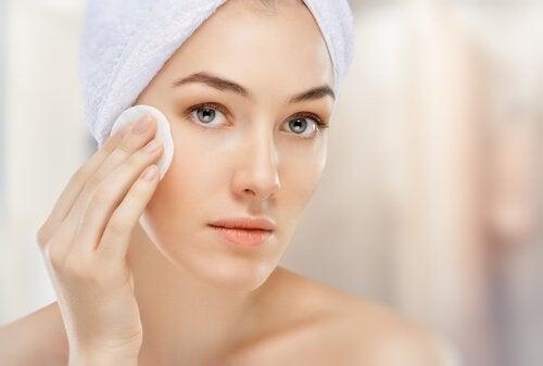 Грижа против бръчките по лицето: Млада жена почиства лицето си с памучен тампон
