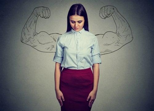 Емоционално силни: млада жена изправена, а зад нея са нарисувани мускулести ръце