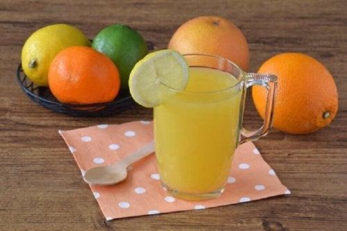 Цитросови плодове на маса и чаша сок от тях