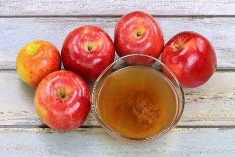 Ябълки на маса и чаша с ябълков оцет