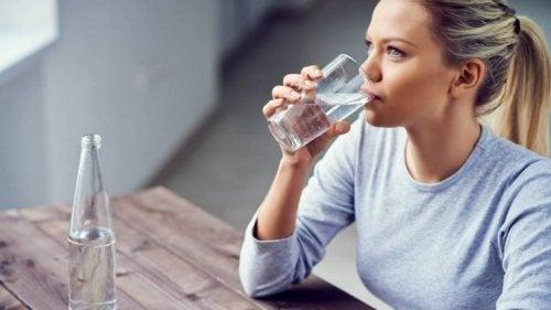 За лесно отслабване: руса млада жена е седнала на маса и пие вода