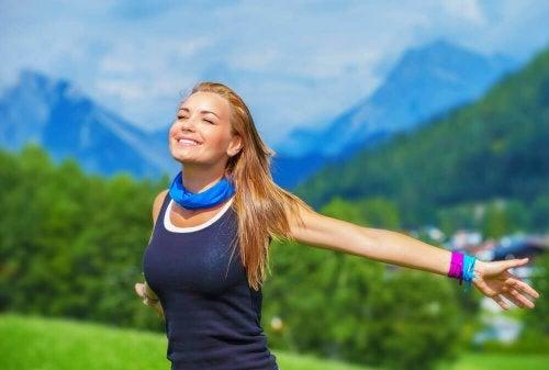 Като пиете повече вода: Една млада и усмихната руса жена с разперени ръце