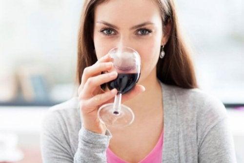 Жена пие чаша червено вино