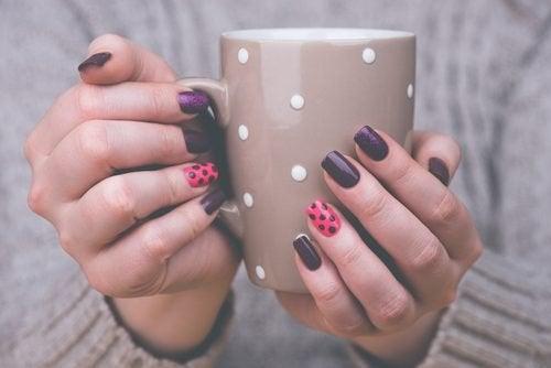 За хубав маникюр: женски ръце с маникюр държат чаша