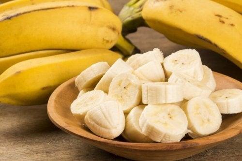 Цели и нарязани банани в чиния на маса
