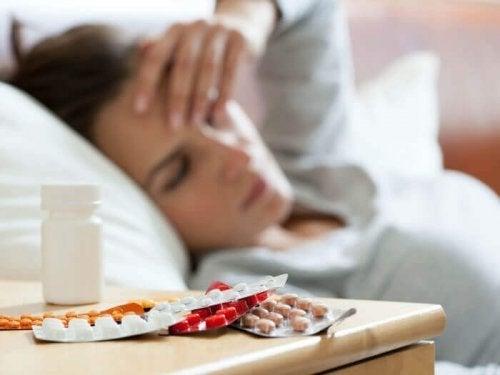 Жена на около 50 е легнала и се държи за главата. Виждат се хапчета на нощно шкафче.
