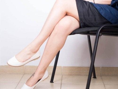 За да избегнете разширените вени: една жена с кръстосани крака седи на стол