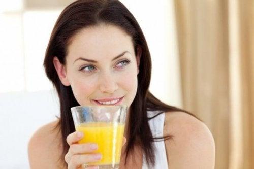 Корите от ананас: една жена пие сок от ананас