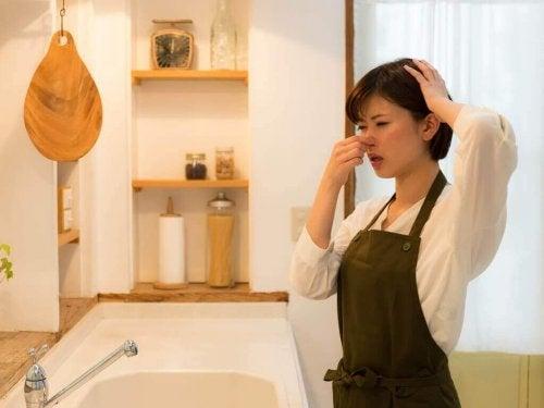 Без лоши миризми: една млада жена с престилка в кухня и си е хванала носа с едната ръка, а с другата главата