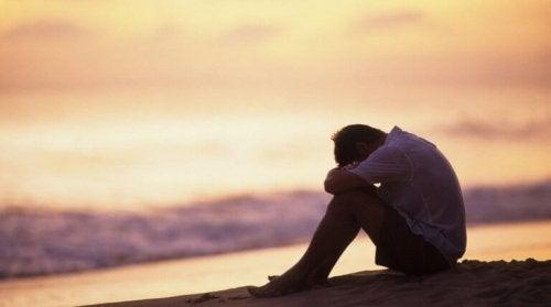 За преодоляване на депресията: мъж седнал на брега на морето при залес слънце
