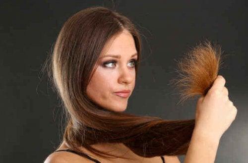 Блестяща и копринена коса: лице на жена. Жената държи краищата на увредена коса