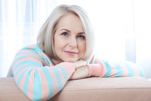 При менопауза: жена на около 50, руса, облегнала се е на диван.