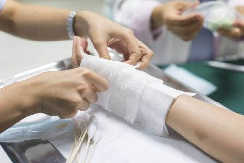 При изгаряне: снимка на ръка и други две ръце я превързват