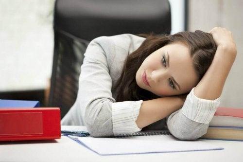Заболяването хипотиреоидизъм: една млада жена се е облегнала на бюро в офиса