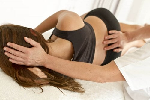 Една жена легнала на болнично легло с гръб. Лекар я преглежда.