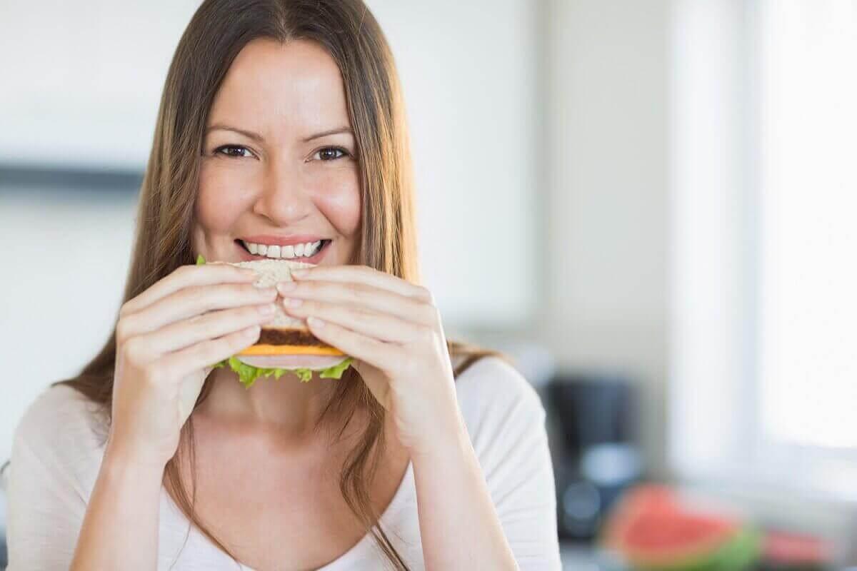 Една млада жена яде сандвич