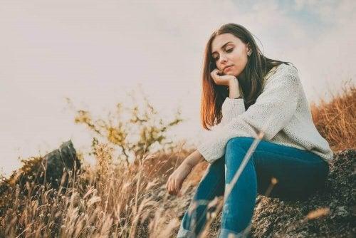 Лавандуловото масло: една млада жена е седнала на поляна в полето
