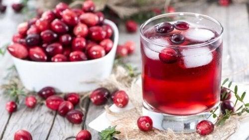 Сок от червена боровинка в стъклена чаша и боровинки плод