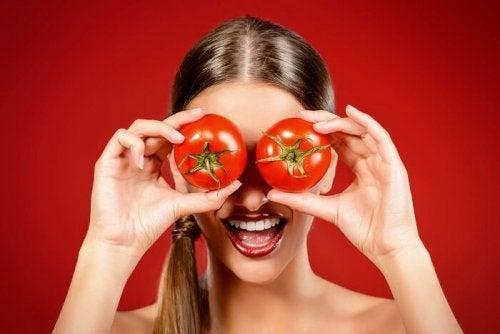 Лице на млада жена, сложила на очите си домати за очи