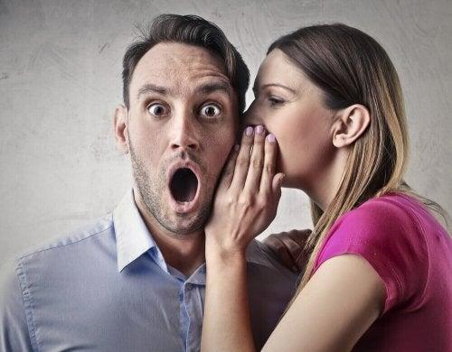 Една жена шепне нещо на ушото на един мъж и клюкарства