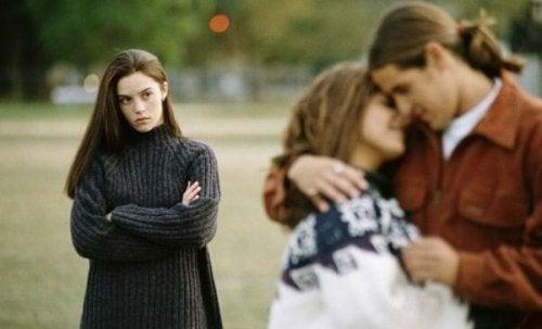 Чувството за самота: прегърнати момиче и момче и едно друго момиче ги гледа