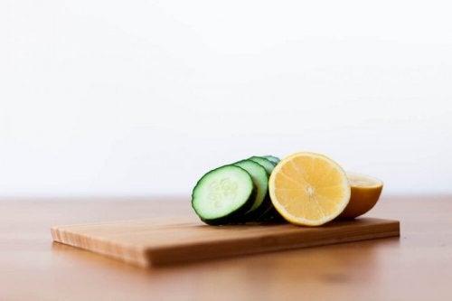 Нарязани лимони и краставица на дъска за рязане