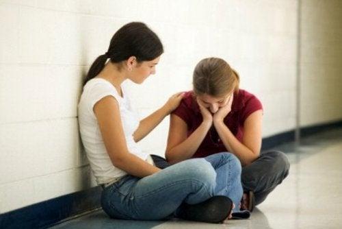 Емоционално нестабилните хора: две момичета са седнали в коридора, на пода, и едното момиче утешава другото.