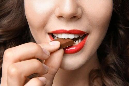 Храни, които повишават настроението: лице на млада жена, която яде шоколад