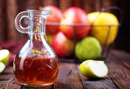 Ябълков оцет в стъклено шише и ябълки