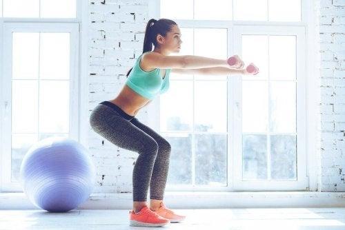Една млада жена прави упражнения с прикляквания