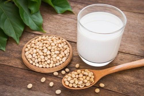 Соево мляко в чаша и семена от соя около нея