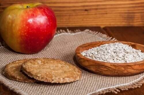 Овесените бисквити: снимка на една червена ябълка и овесени ядки в чиния