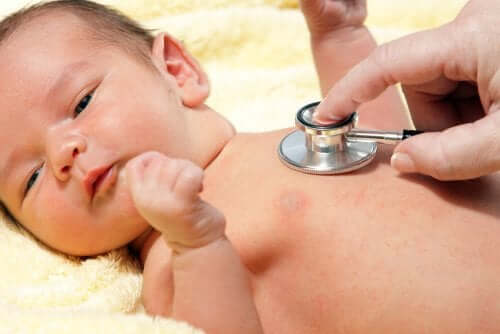 Снимка на бебе, преглеждано от лекар, със слушалка на гърдите на бебето.