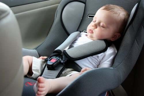 Снимка на бебе, кето спи в бебешка седалка в кола