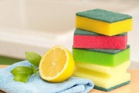 Почистване на тавите на фурната: снимка на половин лимон и до него 4 гъби за почистване и кърпа за почистване
