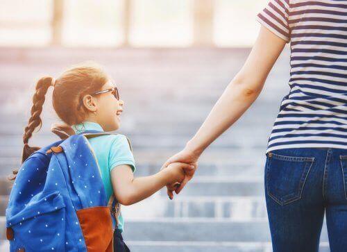 Едно усмихнато момиче и майка му го води на училище