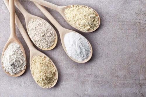 Четири дървени лъжици с различни видове брашно, без глутен
