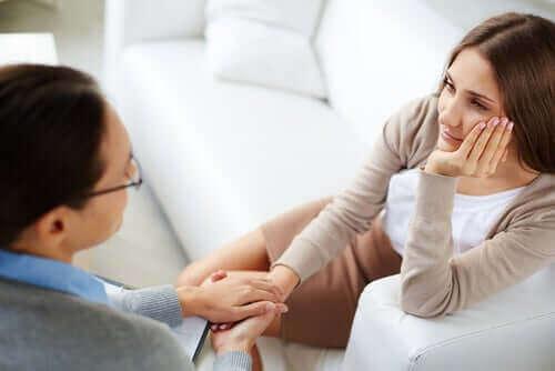 Една разтревожена жена и друга жена, вероятно психолог, и държи ръката