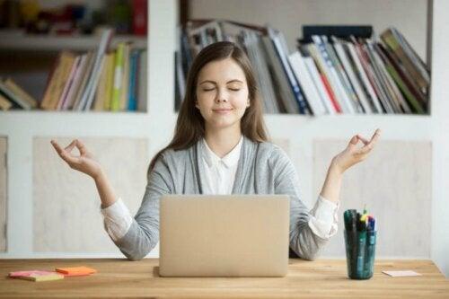 Едно младо момиче пред лаптоп, със затворени очи и разтворени ръце
