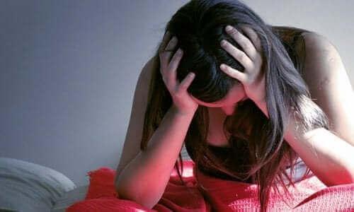 Посттравматичен стрес: една стресирана жена се държи за главата