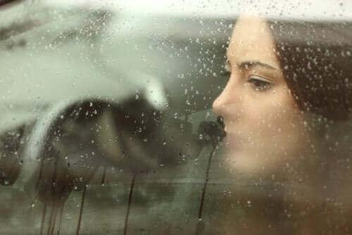 Снимка на лице на тъжна жена, която глед през прозореца, а навън вали дъжд
