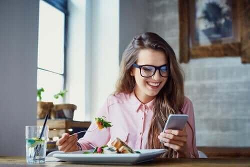 Млада жена яде и се разсейва с телефона