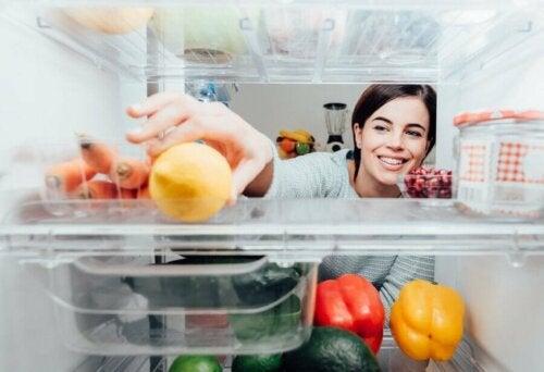 Снимка на отворен хладилник и една млада жена, която се усмихва