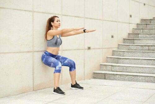 Да останем във форма: една млада жена прави прикляквания до стена