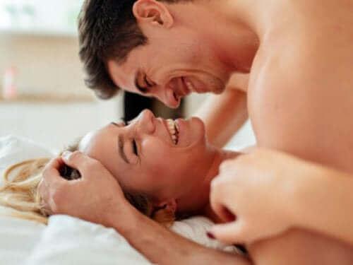 Мъж и жена се смеят и са в леглото интимно
